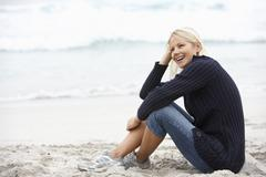 Young Woman On Holiday Sitting On Winter Beach Stock Photos