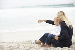 Mother And Daughter On Holiday Sitting On Winter Beach Stock Photos