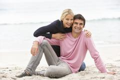 Young Couple On Holiday Sitting On Winter Beach - stock photo