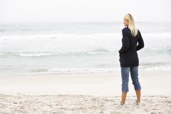 Young Woman On Holiday Standing On Winter Beach - stock photo