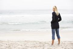 Nuori nainen Holiday Standing On Winter Beach - stock photo
