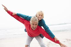 Grandfather Giving Grandson Piggy Back On Winter Beach Stock Photos
