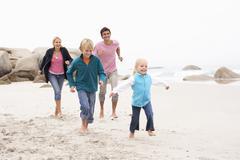 Young Family Running Along Winter Beach Stock Photos