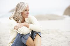 Senior Woman On Holiday Sitting On Winter Beach Stock Photos
