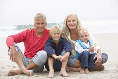 Grandparents And Grandchildren Sitting On Winter Beach Together Stock Photos