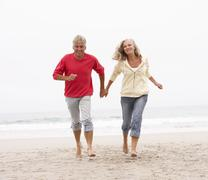 Senior Couple On Holiday Running Along Winter Beach Stock Photos