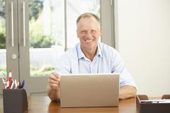 Stock Photo of Middle Aged Man Using Laptop At Home