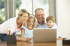 Family Using Laptop At Home Stock Photos