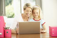 Mother And Daughter Using Laptop At Home Stock Photos