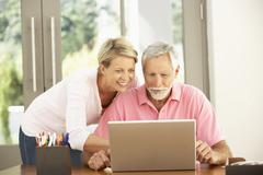 Adult Daughter And Senior Father Using Laptop At Home - stock photo