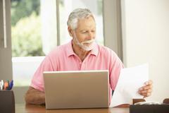 Senior Man Using Laptop At Home Stock Photos