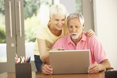 Senior Couple Using Laptop At Home - stock photo