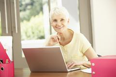Senior Woman Using Laptop At Home - stock photo