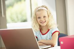 Young Girl Using Laptop At Home - stock photo