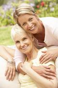 Senior Woman And Adult Daughter Relaxing In Garden Stock Photos