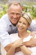 Couple Relaxing In Garden Stock Photos