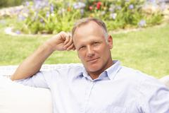 Middle Aged Man Relaxing In Garden Stock Photos