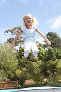Young Girl Jumping On Trampoline In Garden Stock Photos