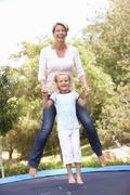 Mother And Daughter Jumping On Trampoline In Garden Stock Photos