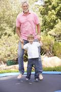 Grandfather And Grandson Jumping On Trampoline In Garden Stock Photos