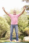 Senior Man Jumping On Trampoline In Garden - stock photo