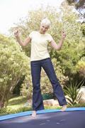 Senior Woman Jumping On Trampoline In Garden - stock photo