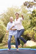 Couple Jumping On Trampoline In Garden Stock Photos
