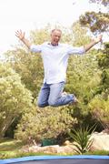 Middle Aged Man Jumping On Trampoline In Garden Stock Photos