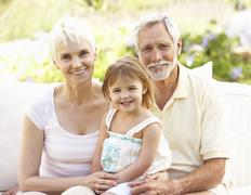Grandparents And Granddaughter Relaxing In Garden - stock photo