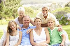Extended Family Relaxing In Garden - stock photo