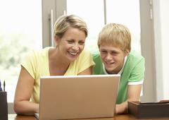 Mother And Teenage Son Using Laptop At Home Stock Photos