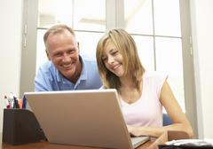 Father And Teenage Daughter Using Laptop At Home - stock photo
