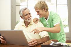 Teenage Grandson Helping Grandfather To Use Laptop At Home - stock photo