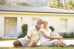 Senior Couple sitting Outside Dream Home Stock Photos