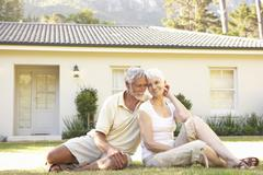 Senior Couple sitting Outside Dream Home - stock photo