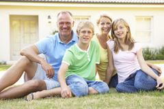 Family Sitting Outside Dream Home - stock photo