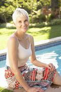 Senior Woman Relaxing By Pool In Garden Stock Photos