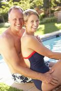 Couple Relaxing By Pool In Garden Stock Photos