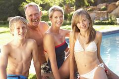 Young Family Relaxing By Pool In Garden Stock Photos