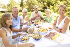 Extended Family Enjoying Meal In Garden Stock Photos