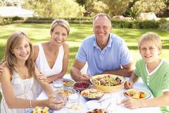 Family Enjoying Meal In Garden - stock photo