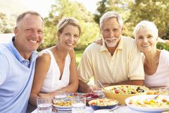 Adult Son And Daughter Enjoying Meal In Garden With Senior Parents Stock Photos