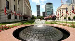 COLUMBUS, OHIO STATEHOUSE - STATE FLAGS, FOUNTAIN IN FOREGROUND - COLORFUL SHOT Stock Footage