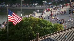 CROWDED STREET_4TH OF JULY_AMERICAN FLAG IN FOREGROUND - AMERICANA Stock Footage