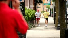 JOGGERS ON SIDEWALK - RUN PAST LENS  Stock Footage