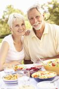Senior Couple Enjoying Meal In Garden Stock Photos