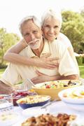 Senior Couple Enjoying Meal In Garden - stock photo