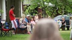 PEOPLE ENJOYING PARADE FROM LAWN - NEIGHBORHOOD Stock Footage