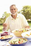 Senior Man Enjoying Meal In Garden Stock Photos