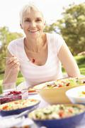 Senior Woman Enjoying Meal In Garden - stock photo